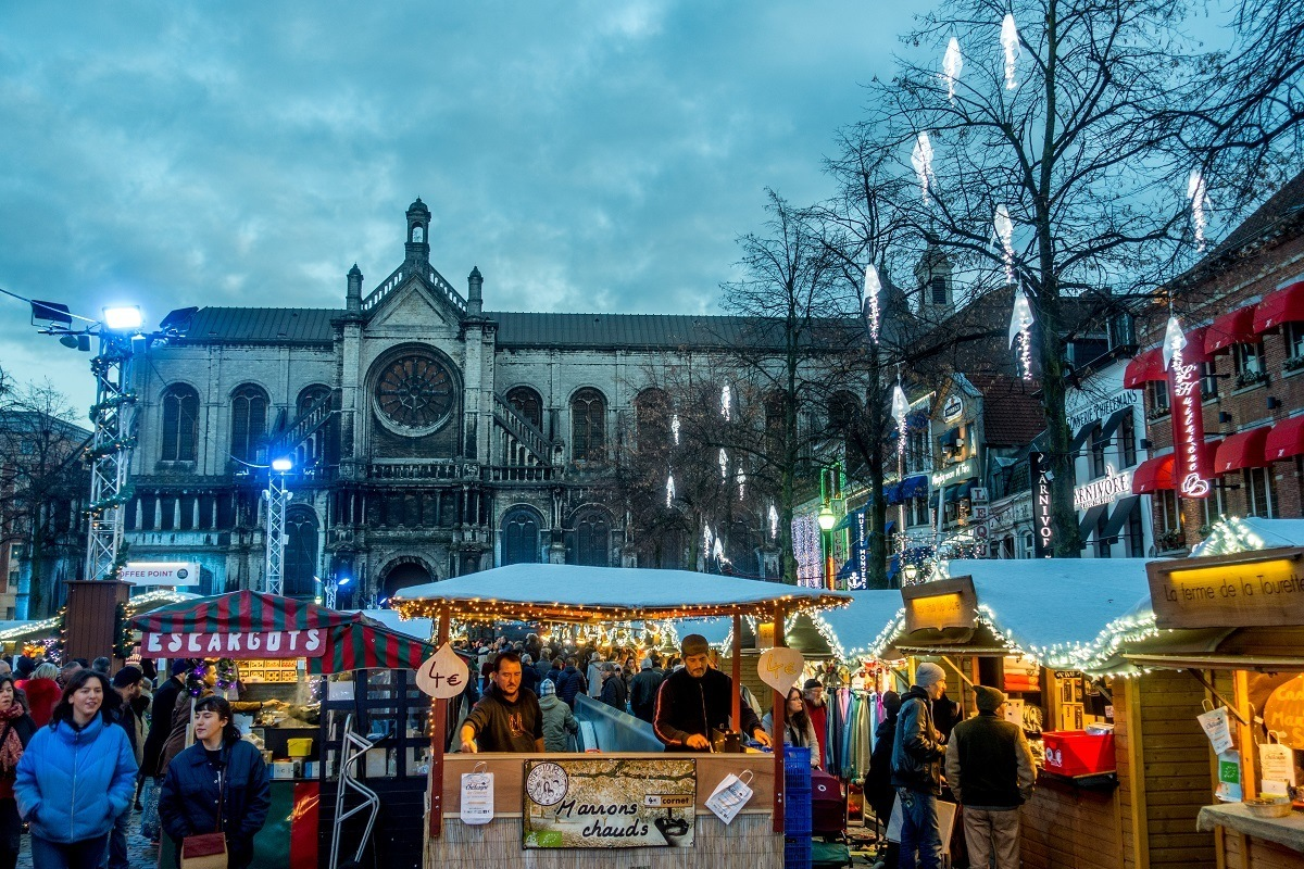 Shoppers at Christmas market stalls with church in the background