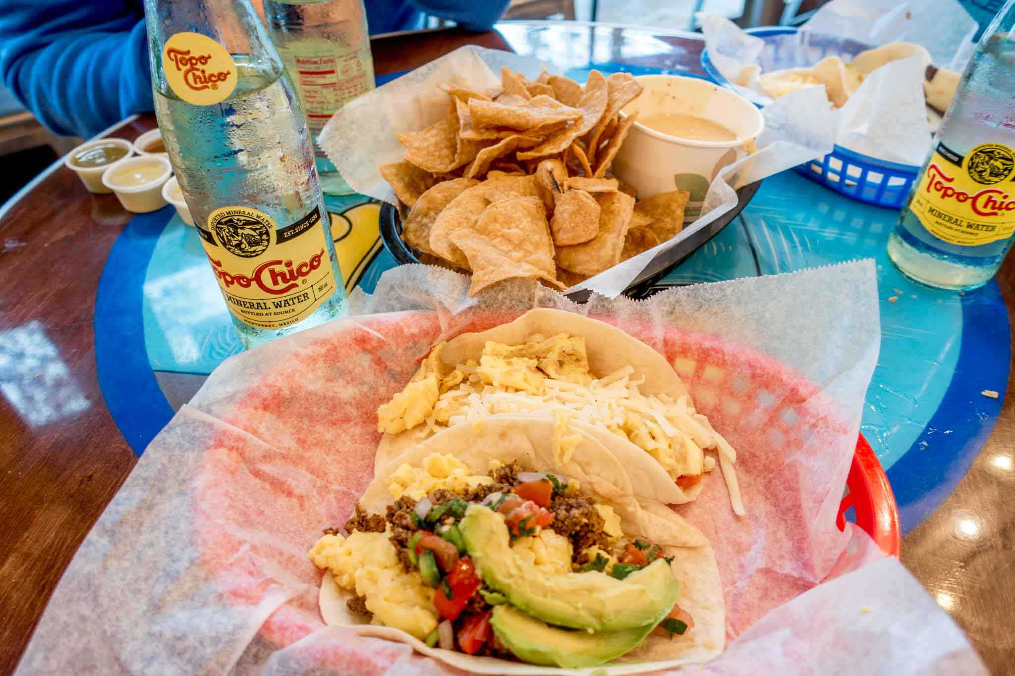 Breakfast tacos, chips, queso, and Topo Chico on a table at Tacodeli