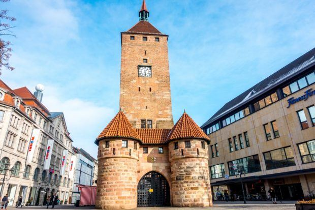 Weisser Turm, the white tower, has a tall, square orange brick tower with the arched city gate immediately in front of it. It is one of the oldest Nuremberg landmarks.