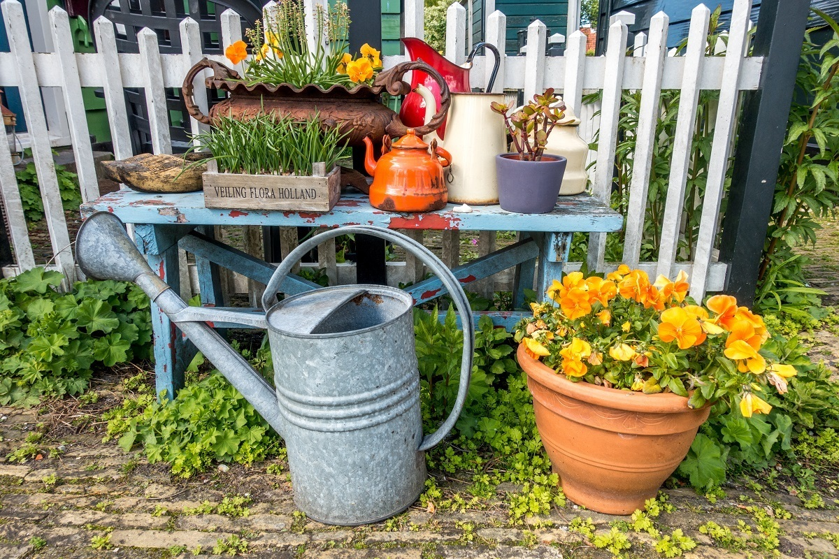 Flowers and decoration on a bench with watering can