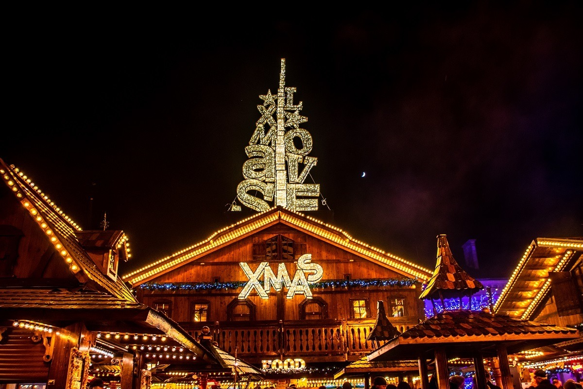 "Wooden food stall chalet covered in amber Christmas lights spelling ""love"" and ""Xmas"" in Place Guillaume II"