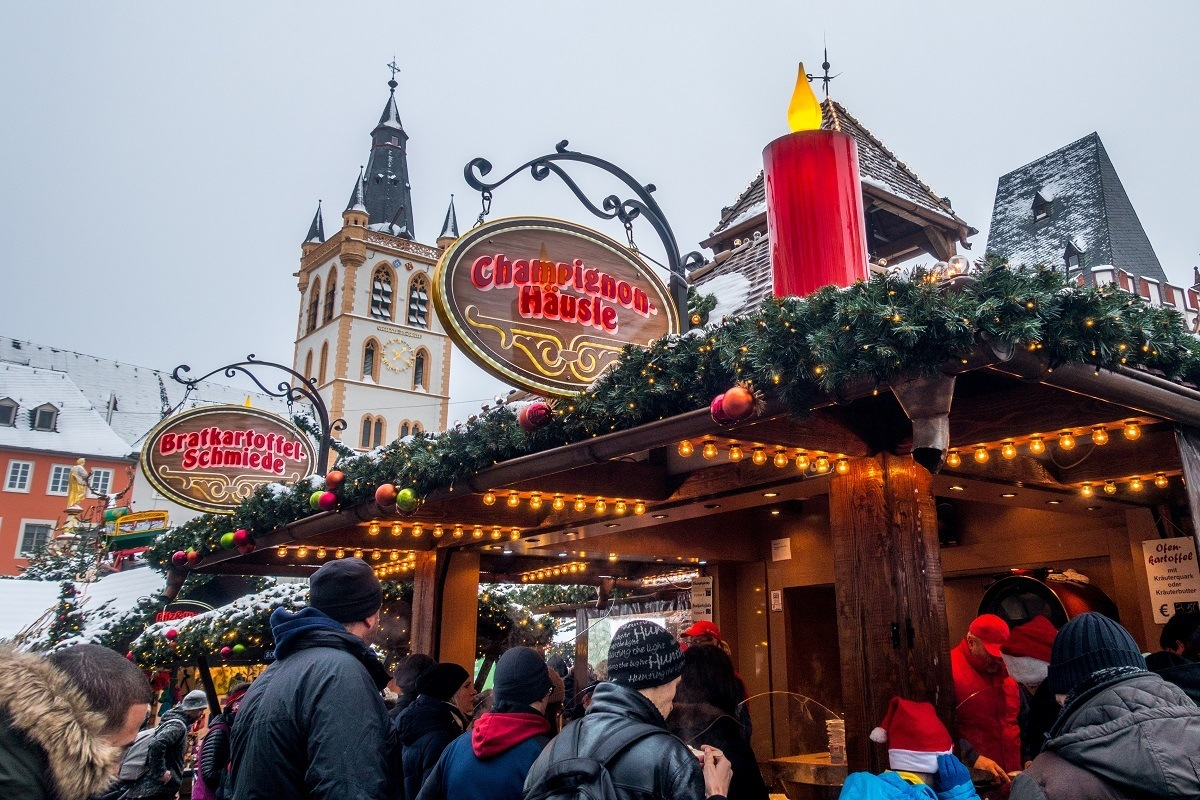 Food stalls covered with garland and lights on an overcast day at the Trier Christmas market in Germany