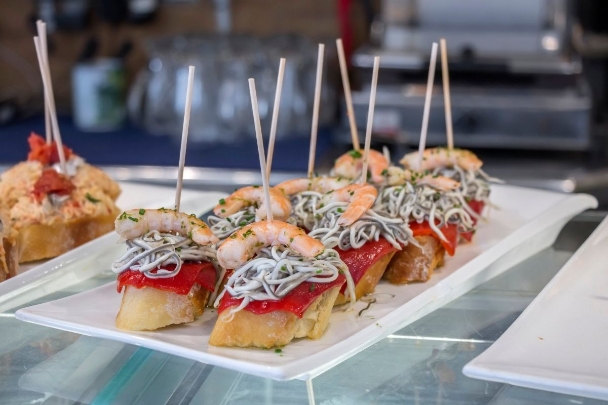 Platter filled with pintxos including shrimp, red peppers, and baby eels | pintxos San Sebastian