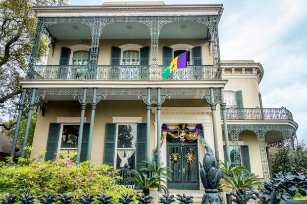 A yellow mansion with green wrought iron balcony and fencing, Colonel Short's Villa in the Garden District is one of the unique New Orleans places to visit