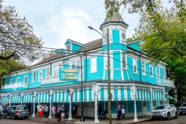 The turquoise and white striped exterior of Commander's Palace. A meal here is what to do in New Orleans for foodies.