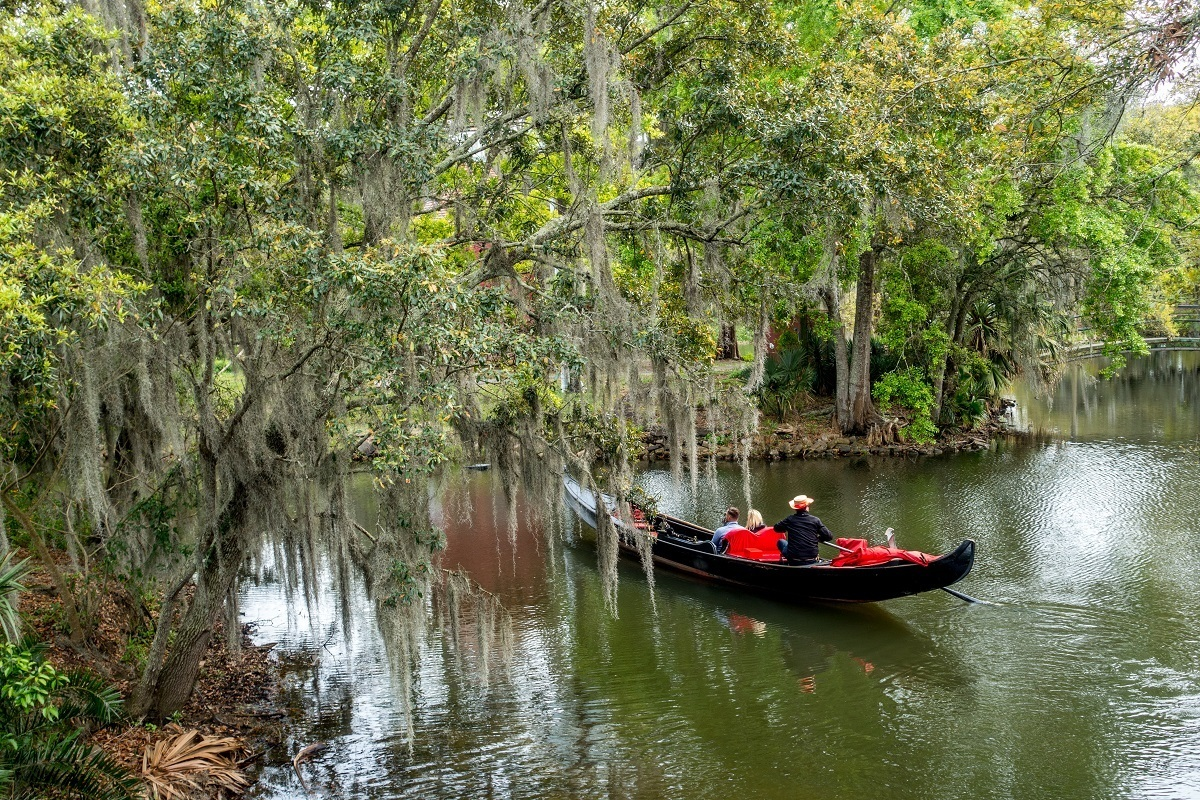 Venetian gondola in a lagoon in City Park surrounded by moss-draped trees