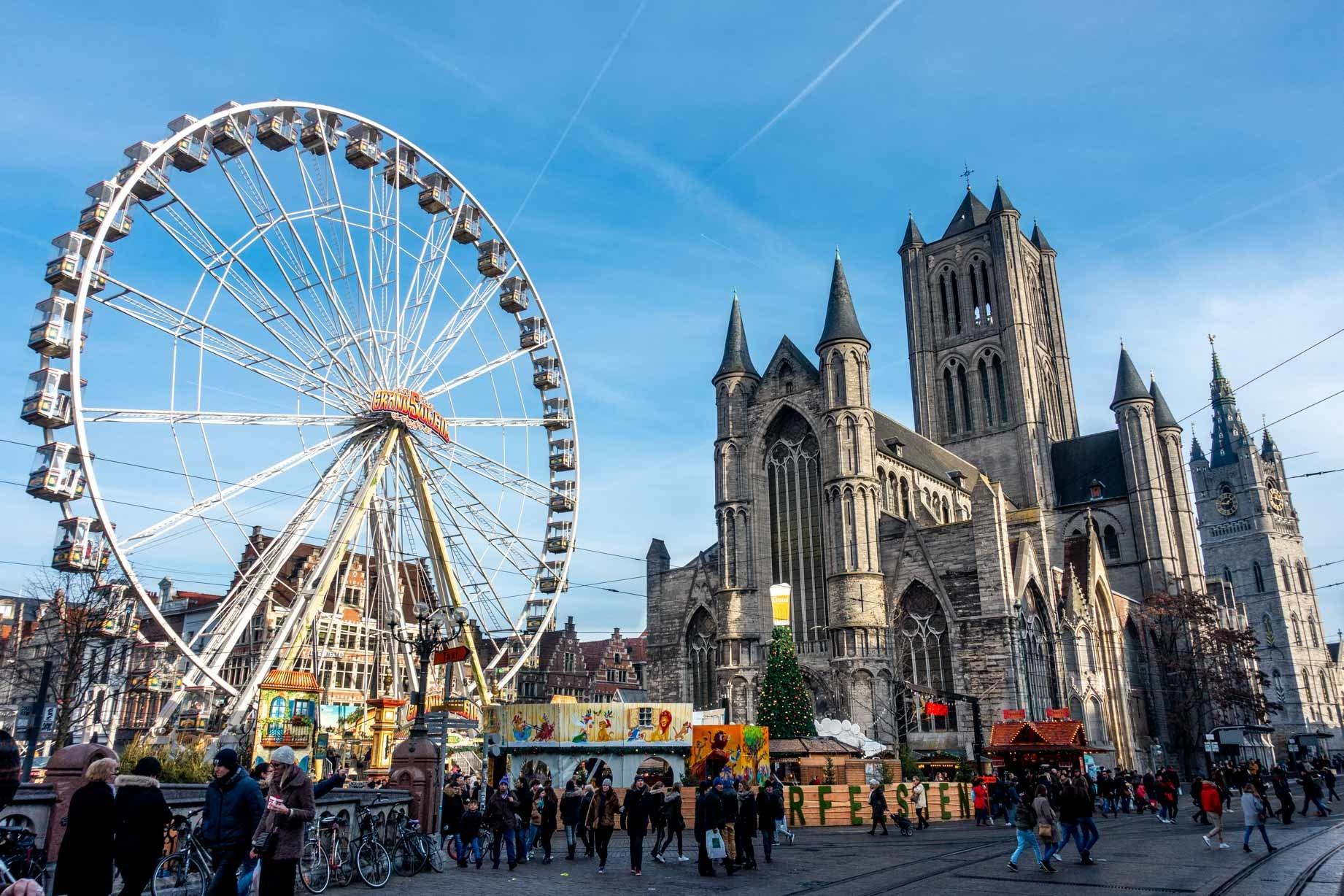 Ferris wheel and booths in front of St Nicholas Church at the Ghent Christmas market in Belgium