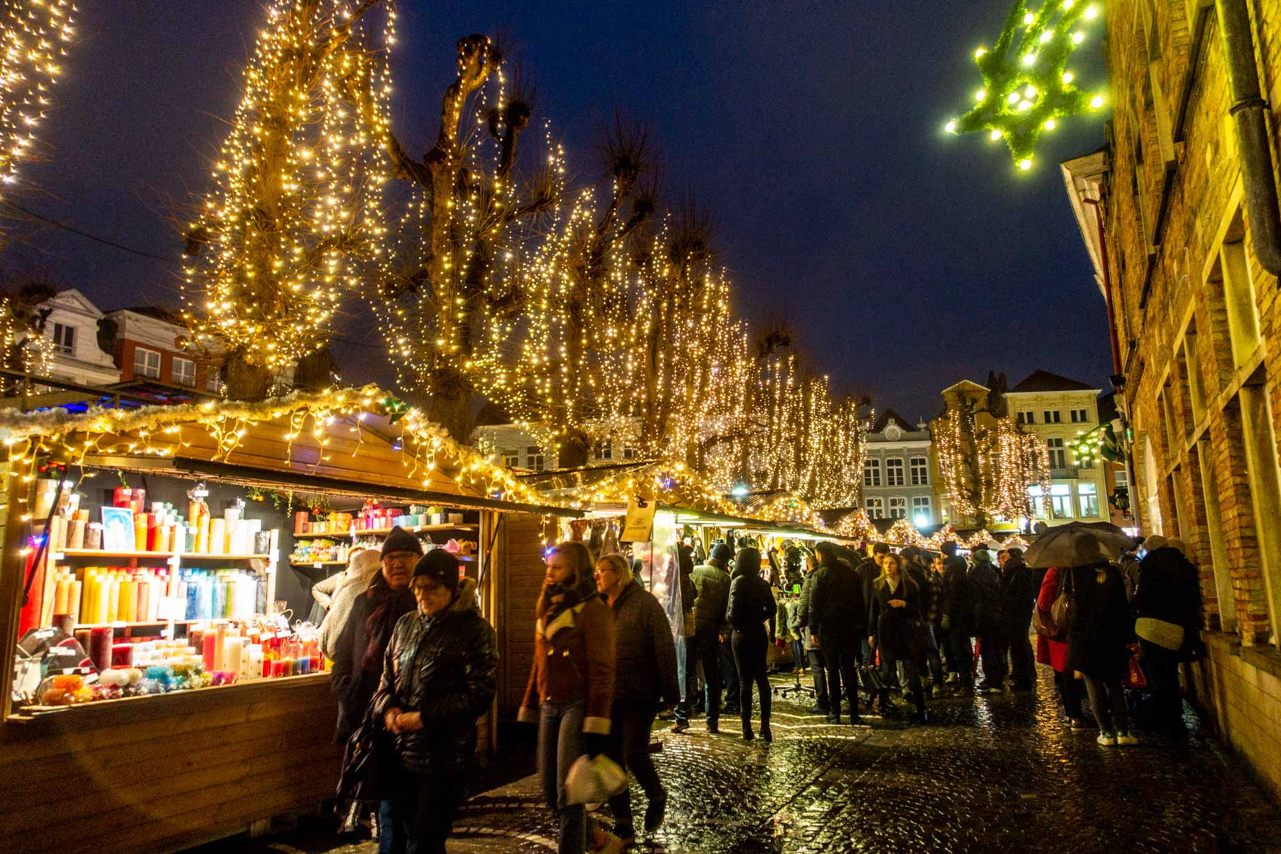 Shoppers peruse the offerings at the Bruges Christmas market at night