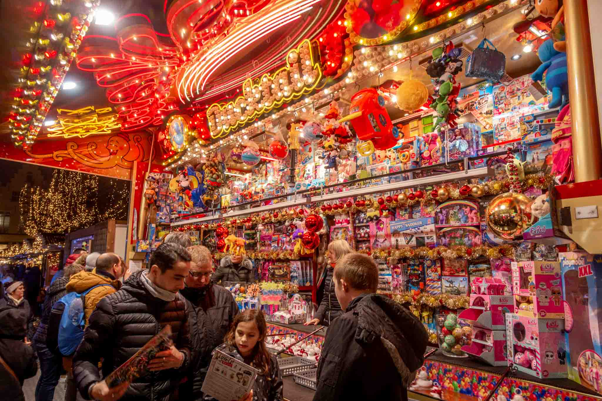 Shopping for toys at one of the brightly lit kiosks at the Bruge Christmas market in Belgium