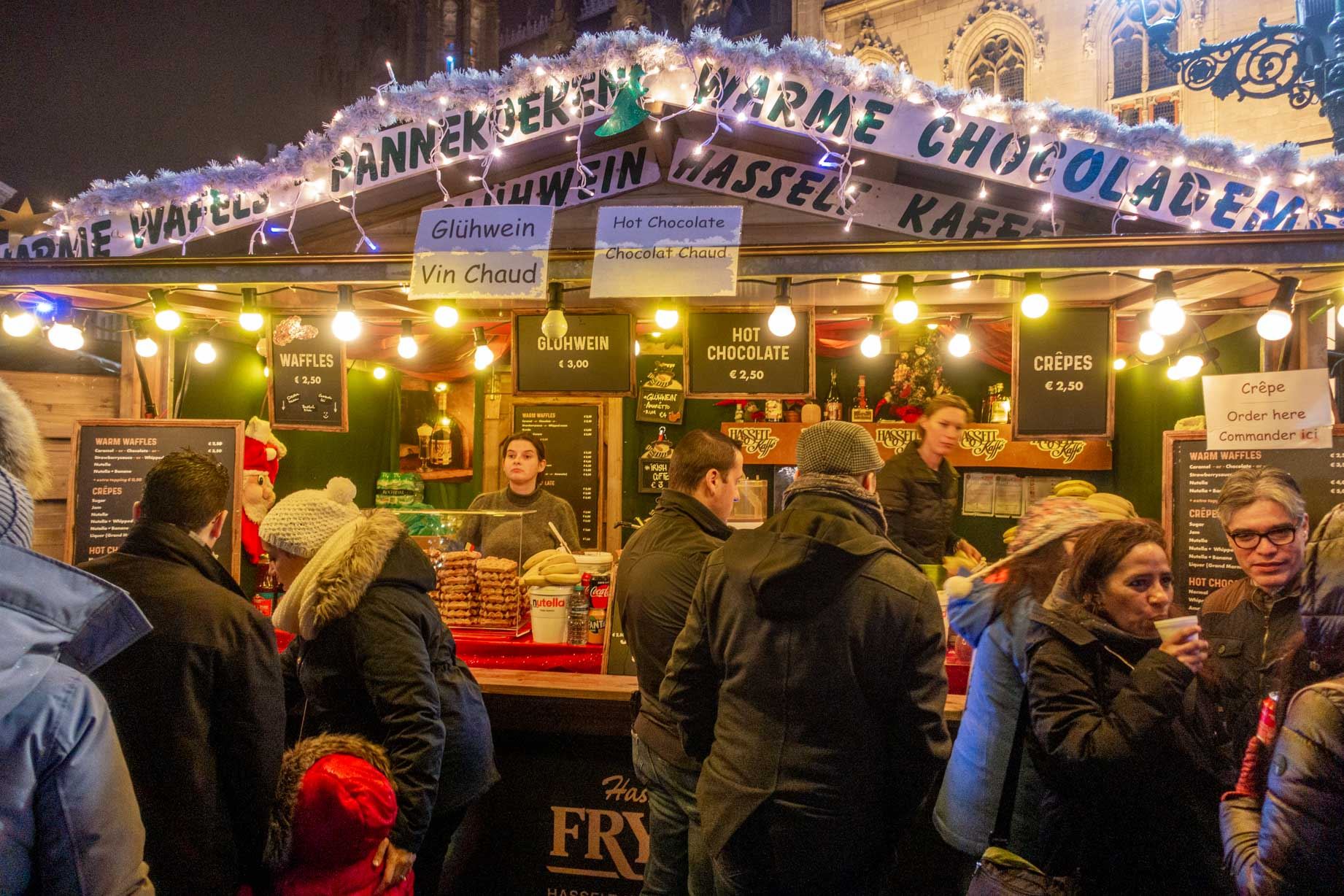 Shoppers lined up to buy drinks at the Christmas market in Bruges Belgium