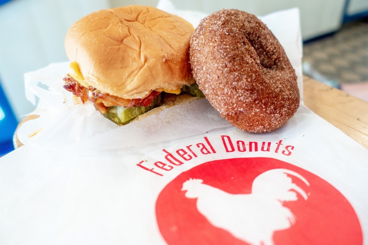 Chicken sandwich and donut on a table with Federal Donuts logo