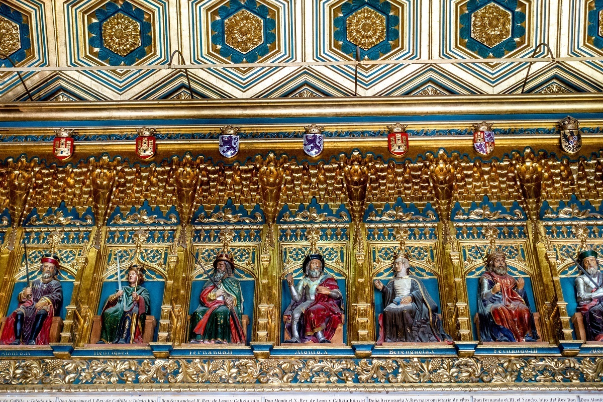 Brightly-colored kings of Castile carved along ceiling in the Room of the Kings
