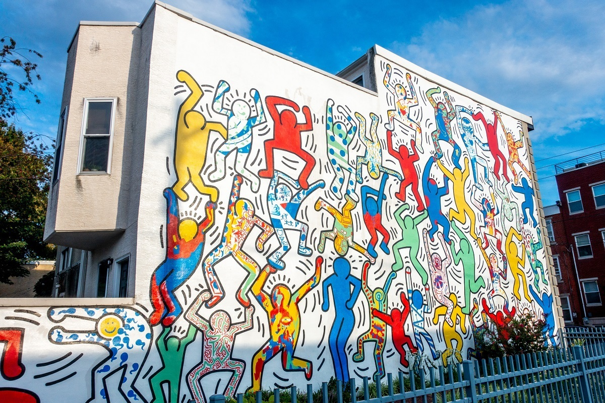 Colorful cartoon people on street art mural by Keith Haring