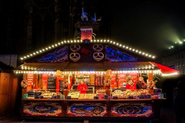 One of the Alsatian food stands selling pretzels near the Cathedral is lit up at night at the Strasbourg France Christmas market