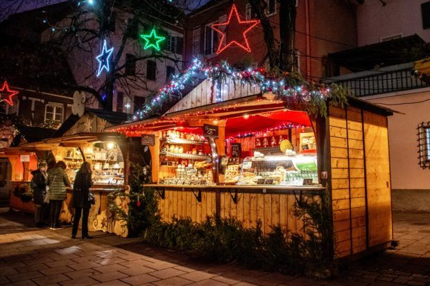 Stand selling cheese that is lit up at night with red and green Christmas lights in Place des Meuniers, part of the Strasbourg Noel market