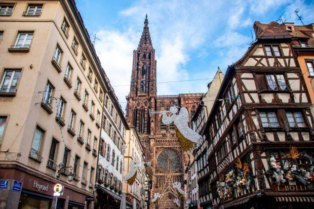 Christmas lights in the shape of angles hang in front of the Strasbourg Cathedral