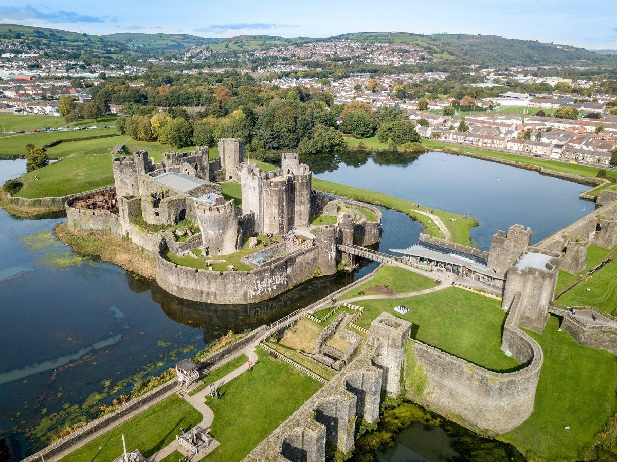 Aerial view of the towers, bridge, and water defenses surrounding in large medieval Caerphilly Castle in southern Wales