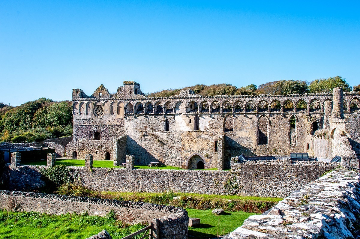 Ruins of a 14th-century stone palace with numerous niche windows and intact walls. The Bishops Palace in St. Davids is one of the prettiest places to visit in South Wales.