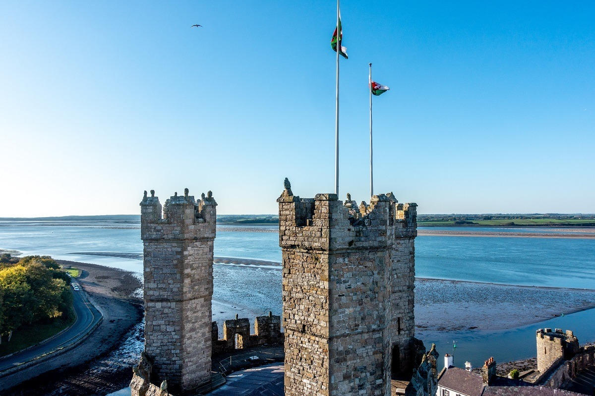Ancient stone towers of Caernarfon Castle topped with Welsh flags