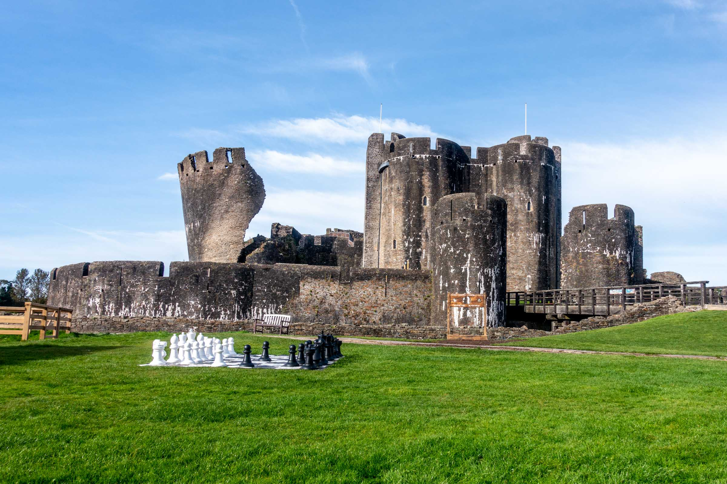 View of the stone towers of Caerphilly Castle with a large lawn chess set in the foreground