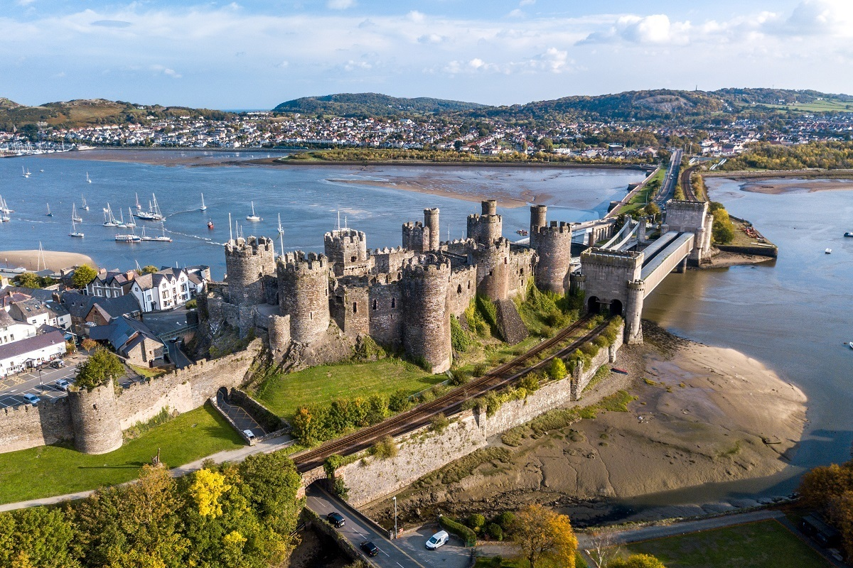 Drone photo of one of the top Wales landmarks--Conwy Castle (a large stone castle) and its drawbridge and harbor taken from above.