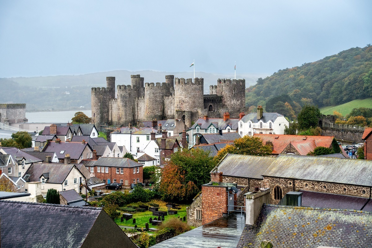 The medieval stone towers of Conwy Castle stick up above the surrounding town on a rainy day. The ancient castles are some of the best places to visit in Wales.