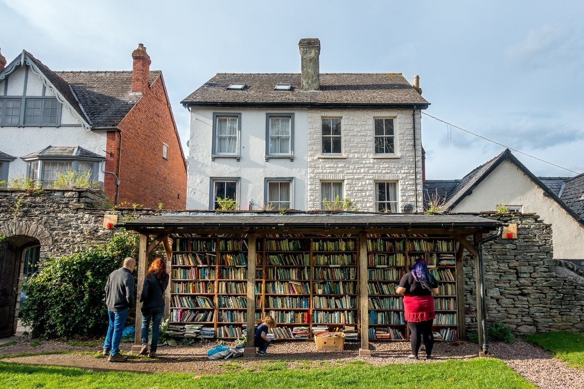 People browsing bookshelves filled with books outdoors in Hay-on-Wye, the top place in Wales for book lovers