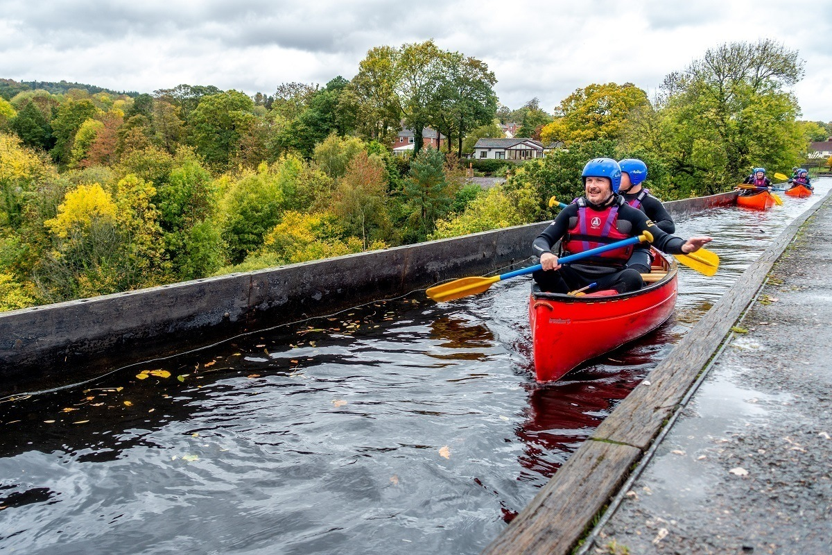 Close up of kayaker wearing a helmet paddling over the Pontcysyllte Aqueduct, one of the top attractions in Wales