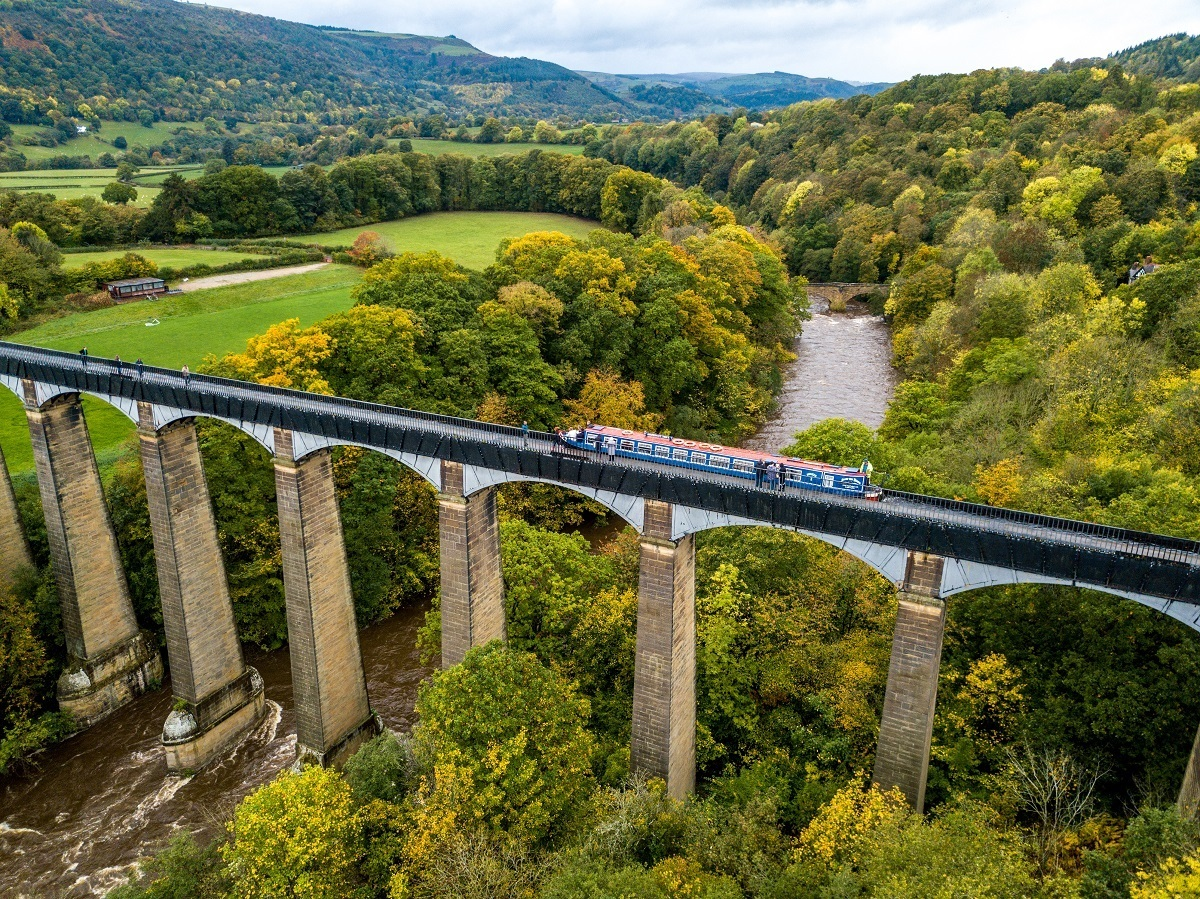 Aerial photos shows the elevated Pontcysyllte Aqueduct carrying a boat and crossing over the river far below. It's one of the best of Wales attractions.