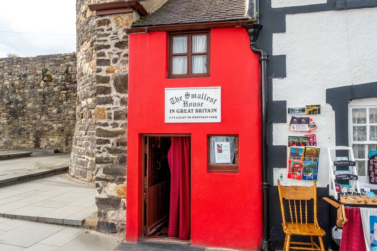 TThe Quay House painted red with a sign saying it is the smallest house in Britain