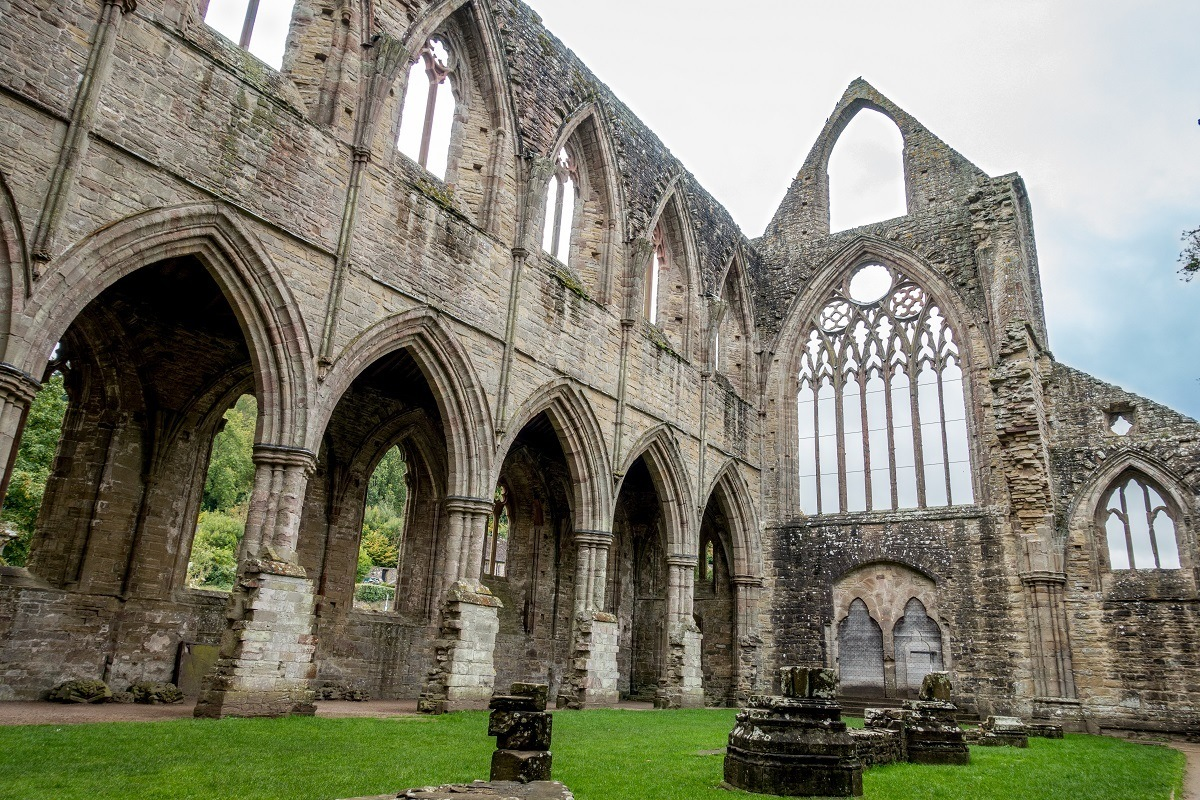 Ruins of Tintern Abbey, a stone church with arches and intricate window frames