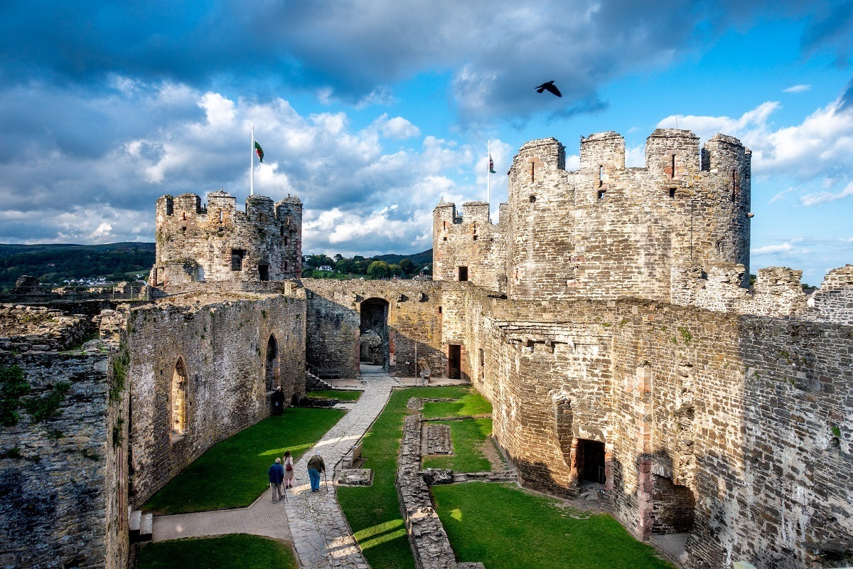 Set against a darkening sky, stone towers and grass-filled courtyard of Conway Castle, one of the top Welsh places to visit