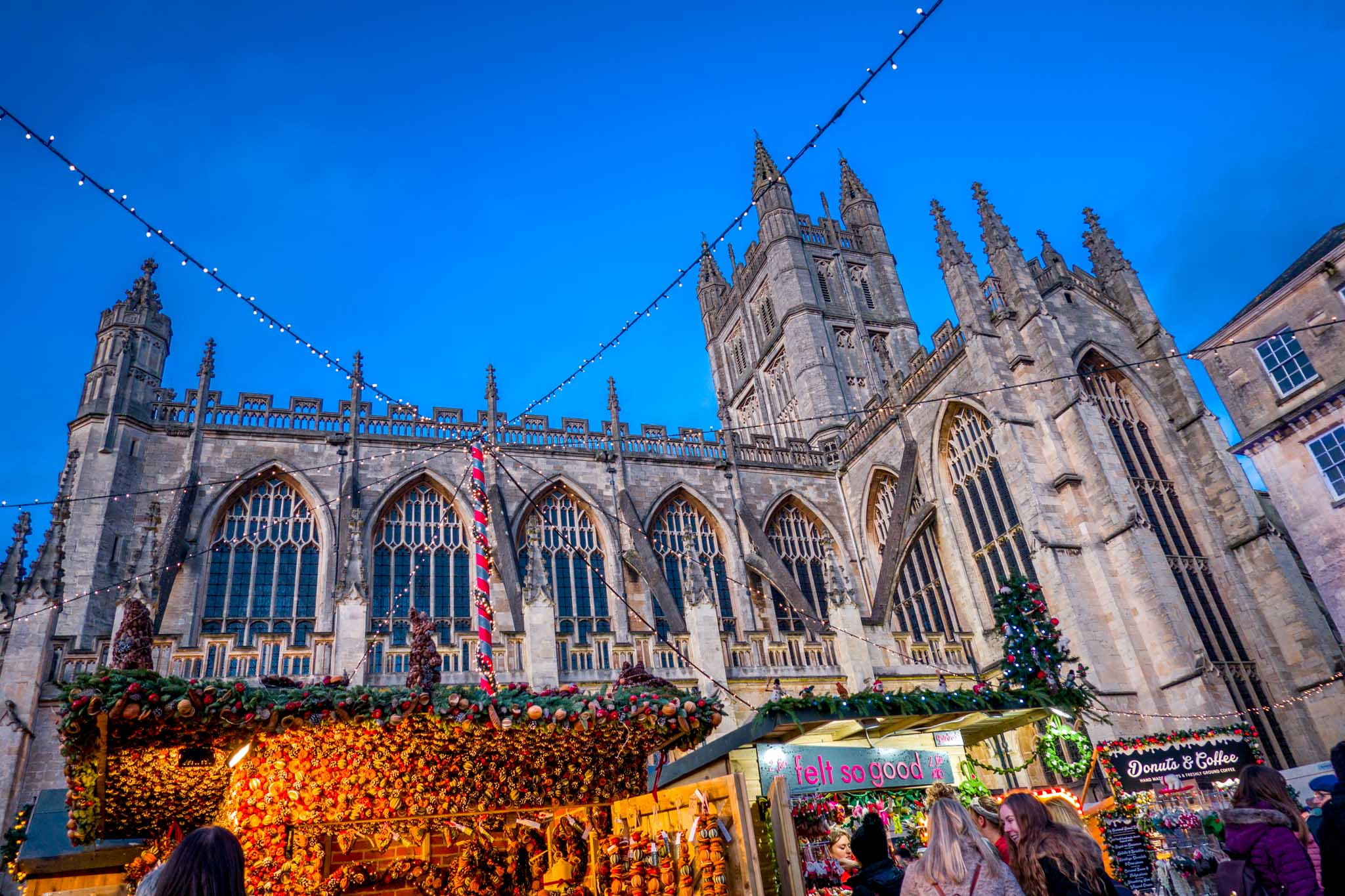 Stalls of the Bath Christmas market lit up at sunset in front of the large stone Bath Abbey