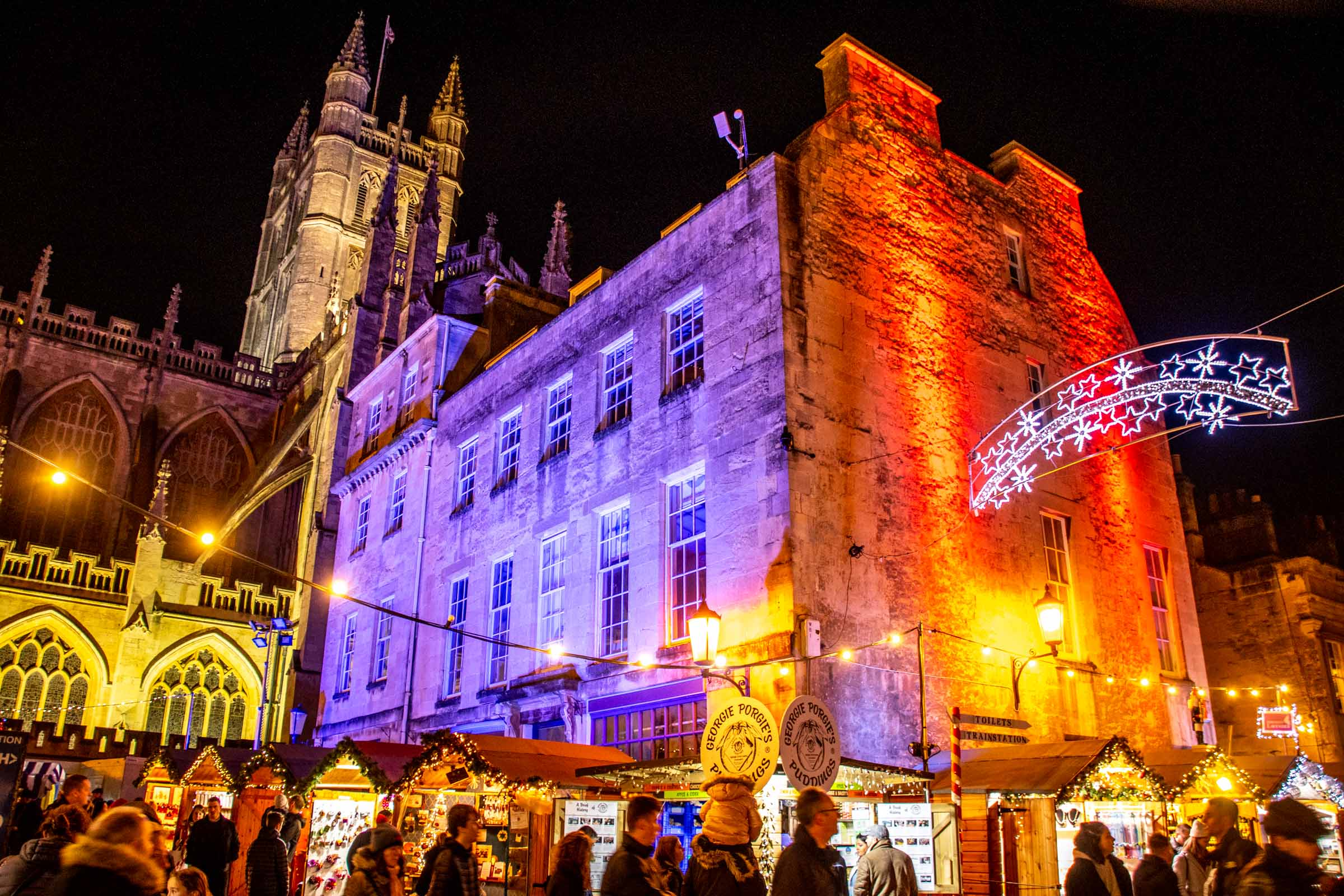 People attending the Bath Christmas market at night in front of Bath Abbey, which is lit up on purple and red lights