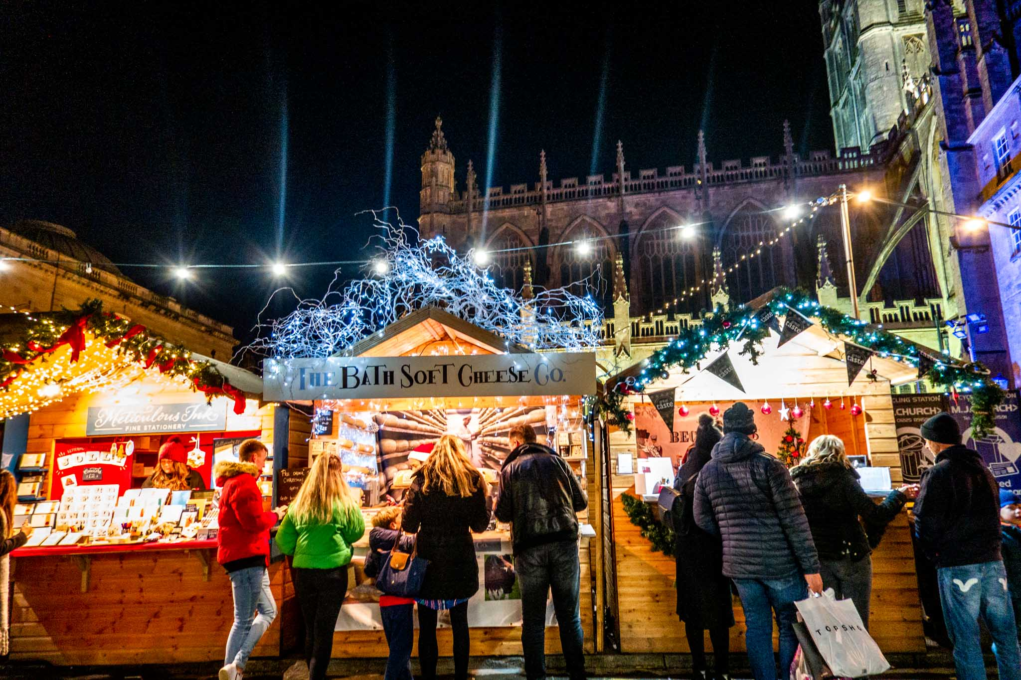 Wooden chalets lit up at night and shoppers in front of Bath Abbey at the Bath Christmas market