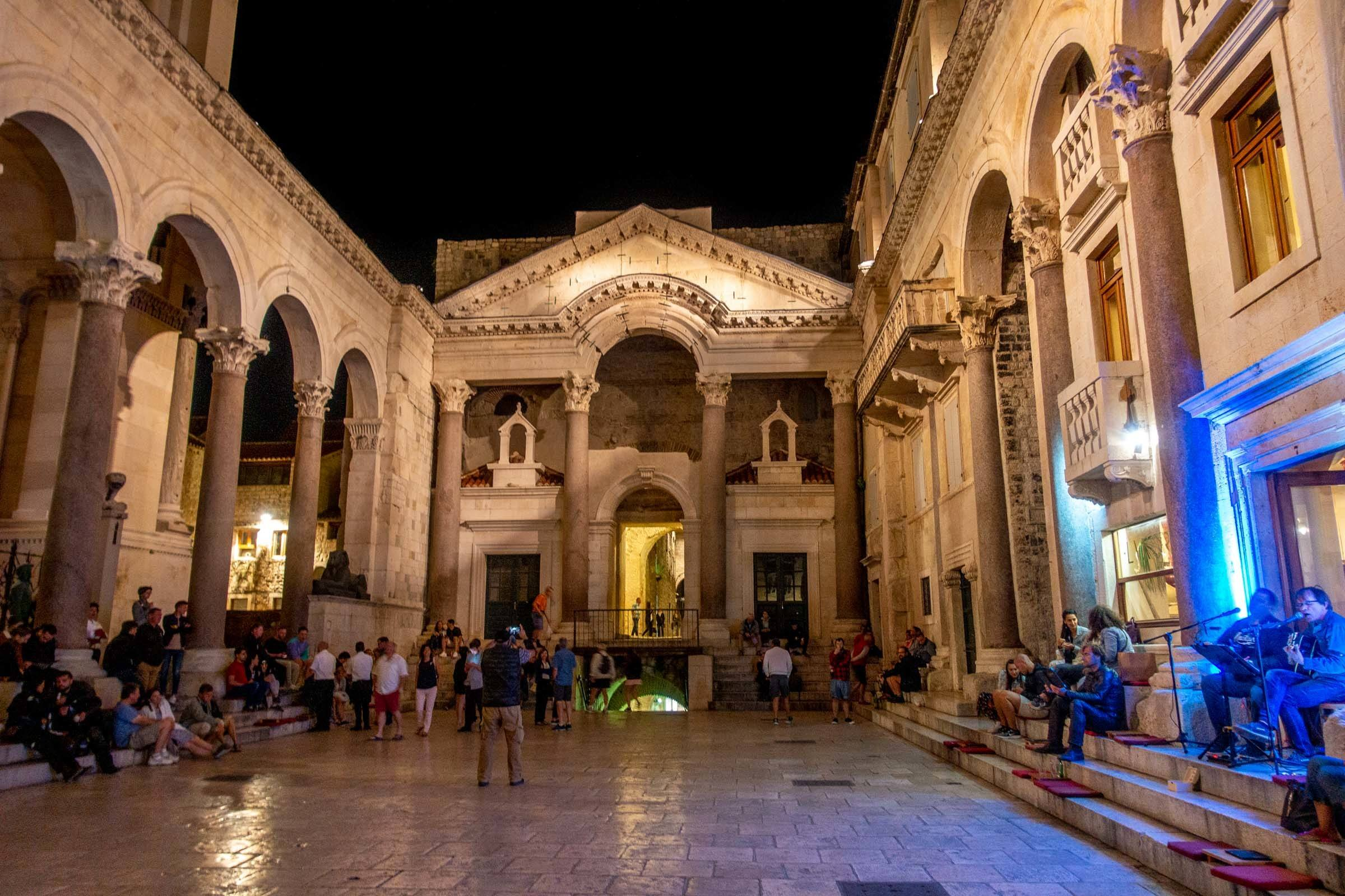 Marble peristyle courtyard of Diocletian's Palace filled with people at night