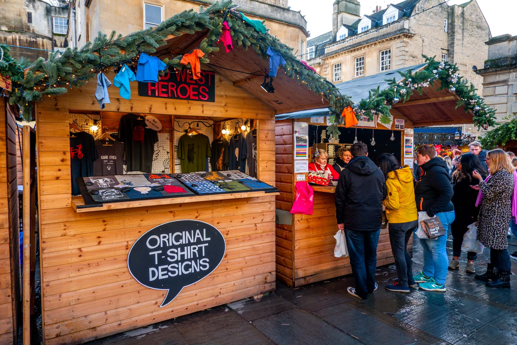 People shopping and eating at wooden chalets at the Christmas market in Bath England