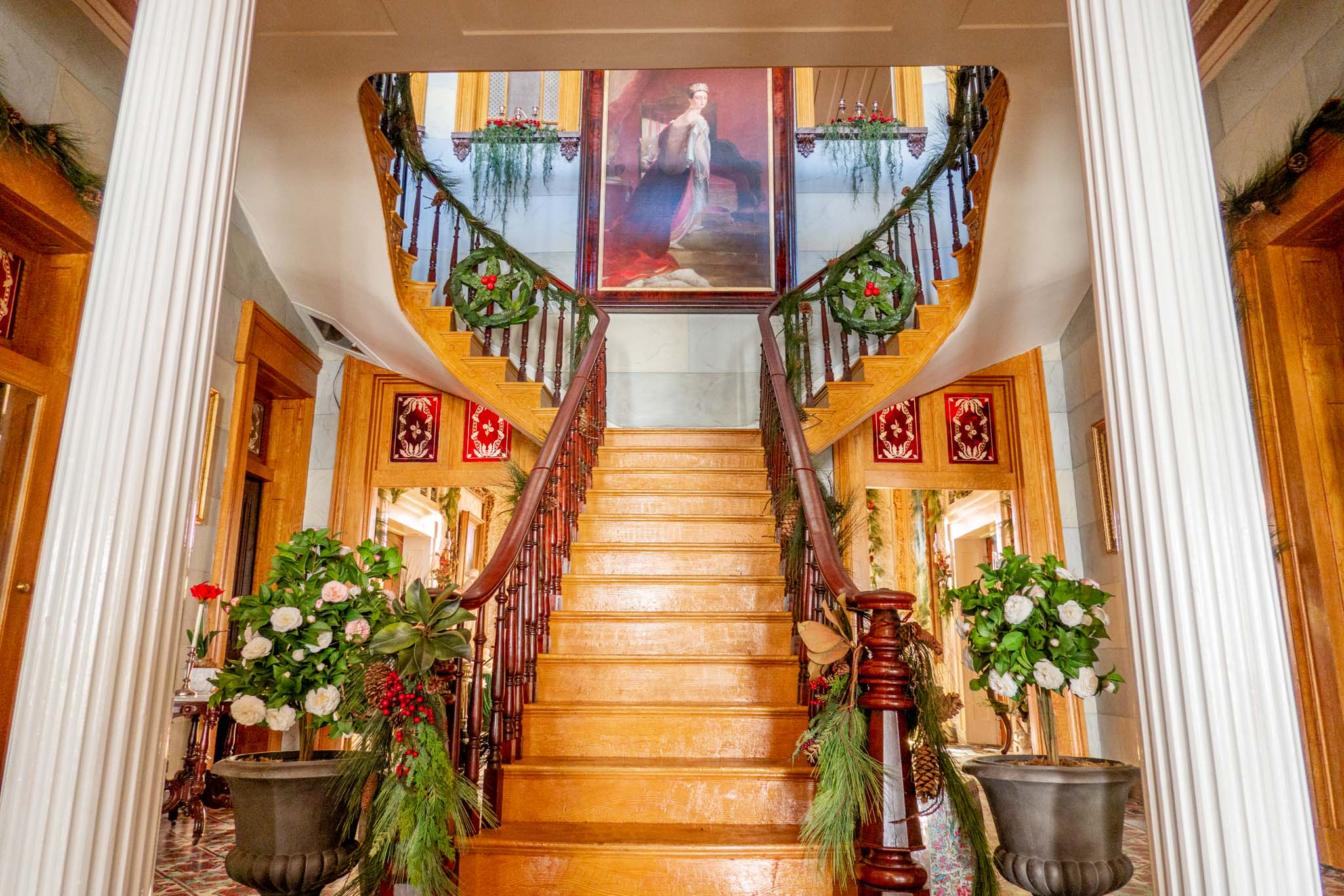 Large wooden staircase with a portrait at the top