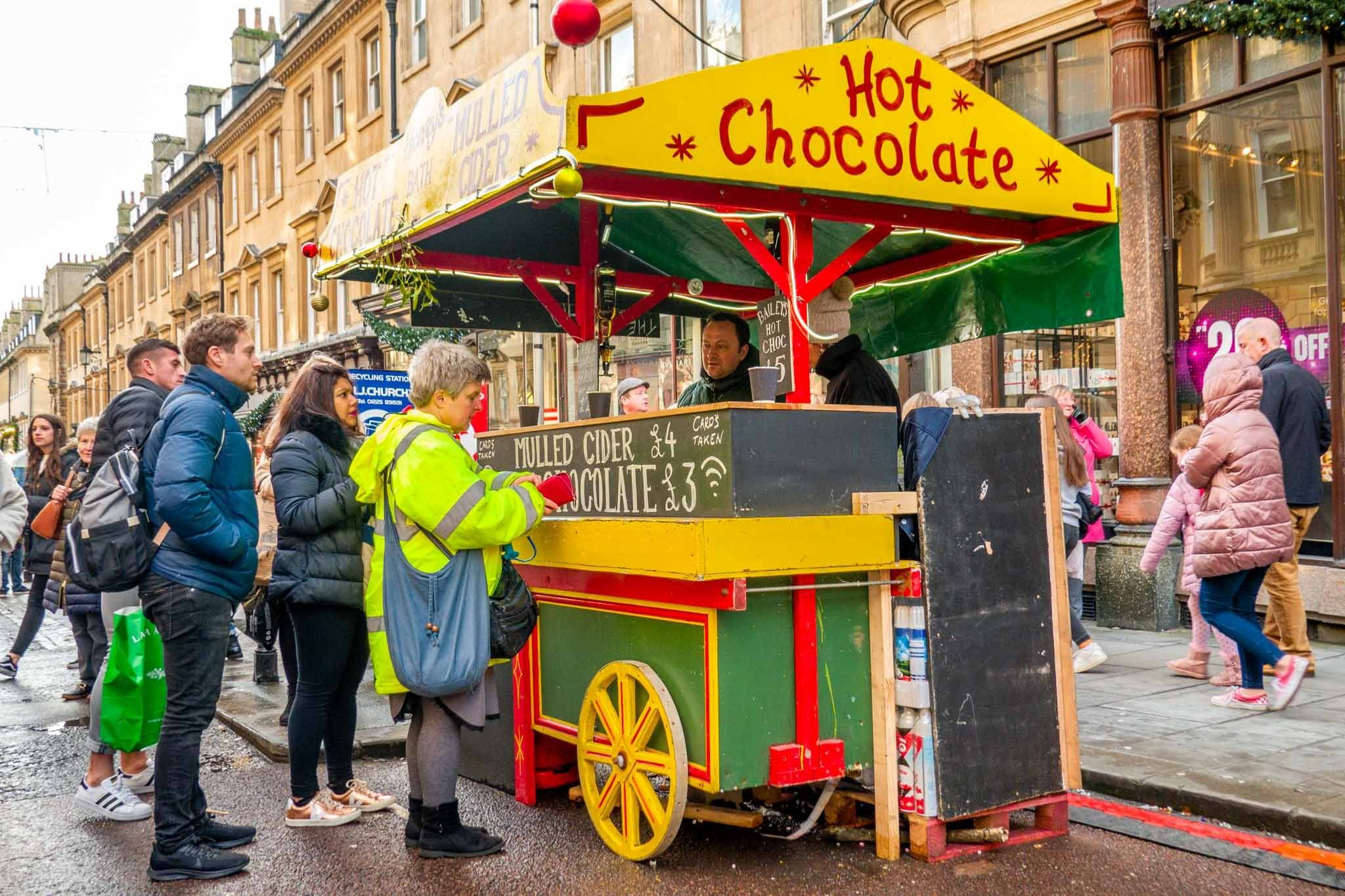 People standing at yellow and green hot chocolate cart in the street in Bath, England