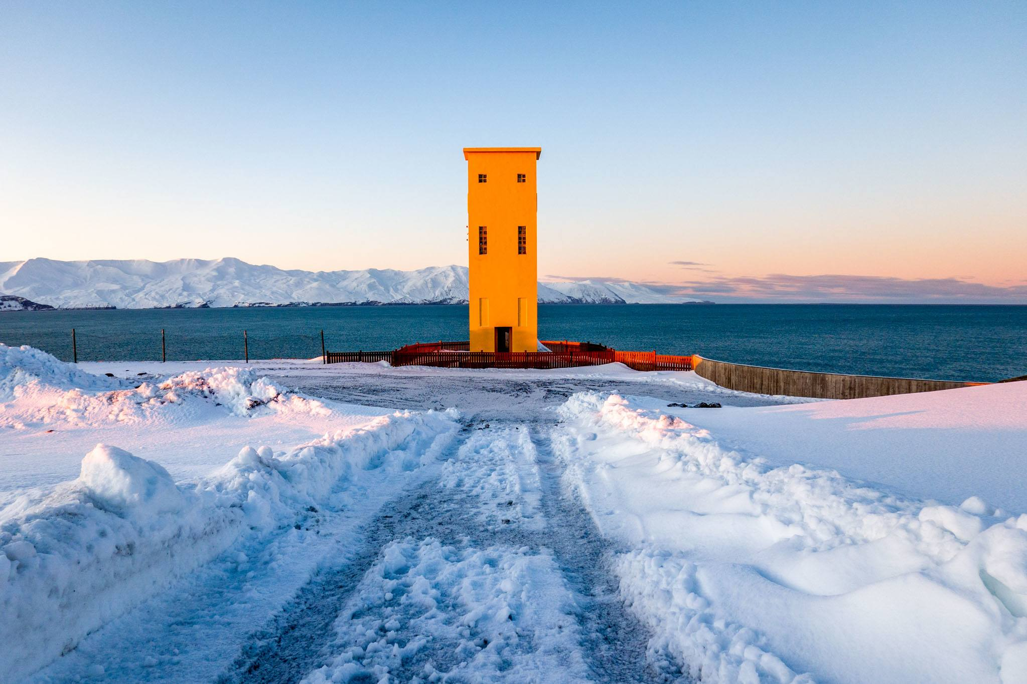 Big yellow Husavik lighthouse in the snow adjacent to the entrance of GeoSea