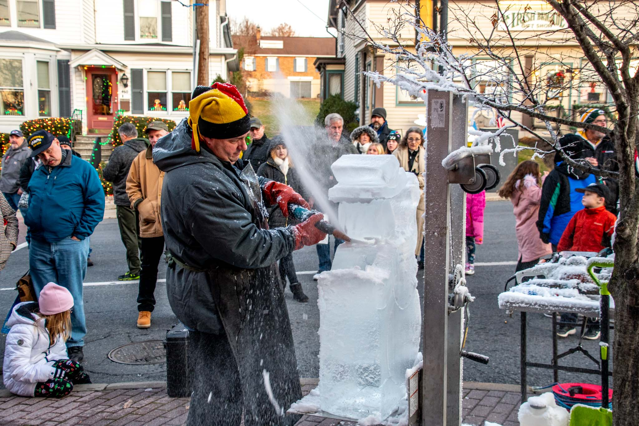 Man carving ice block into a snowman on the streets of Gettysburg