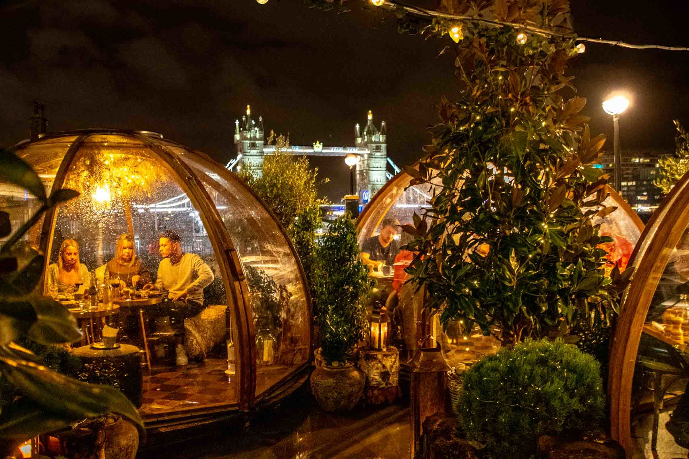 People sitting in transparent igloos overlooking the famous Tower Bridge in London