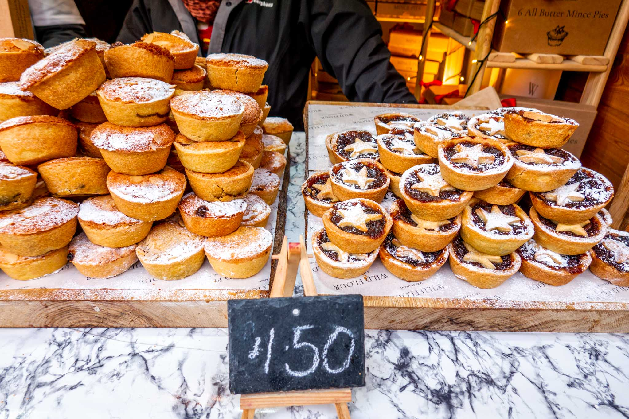Stacks of small mince pies for sale at the Christmas market in Bath UK