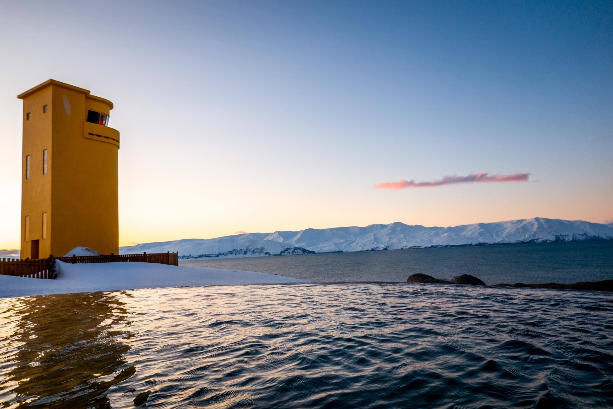 Iconic yellow lighthouse of Husavik next to the Iceland thermal baths of GeoSea