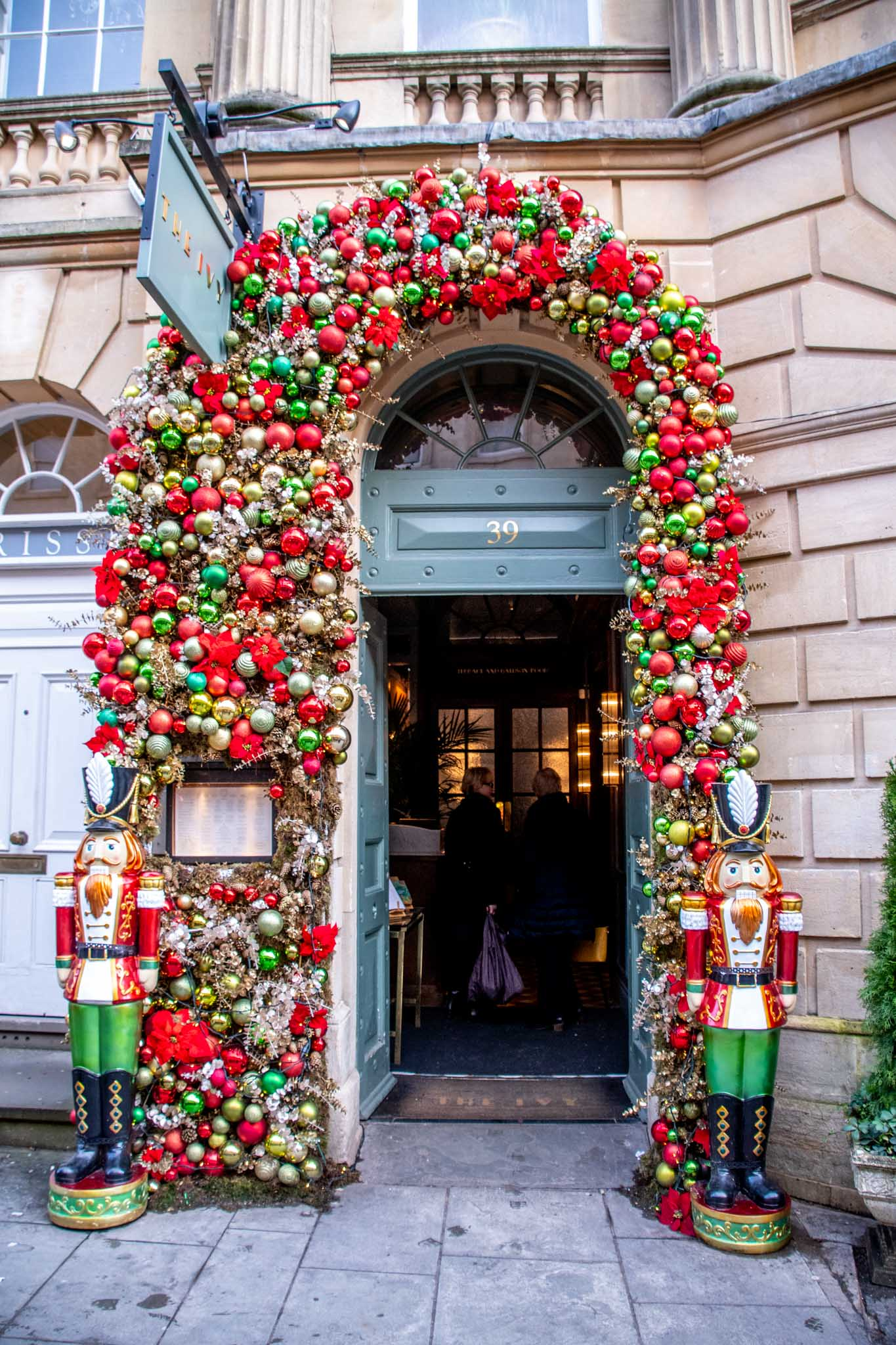 Doorway of The Ivy covered in red and green ornaments and flanked by two nutcrackers