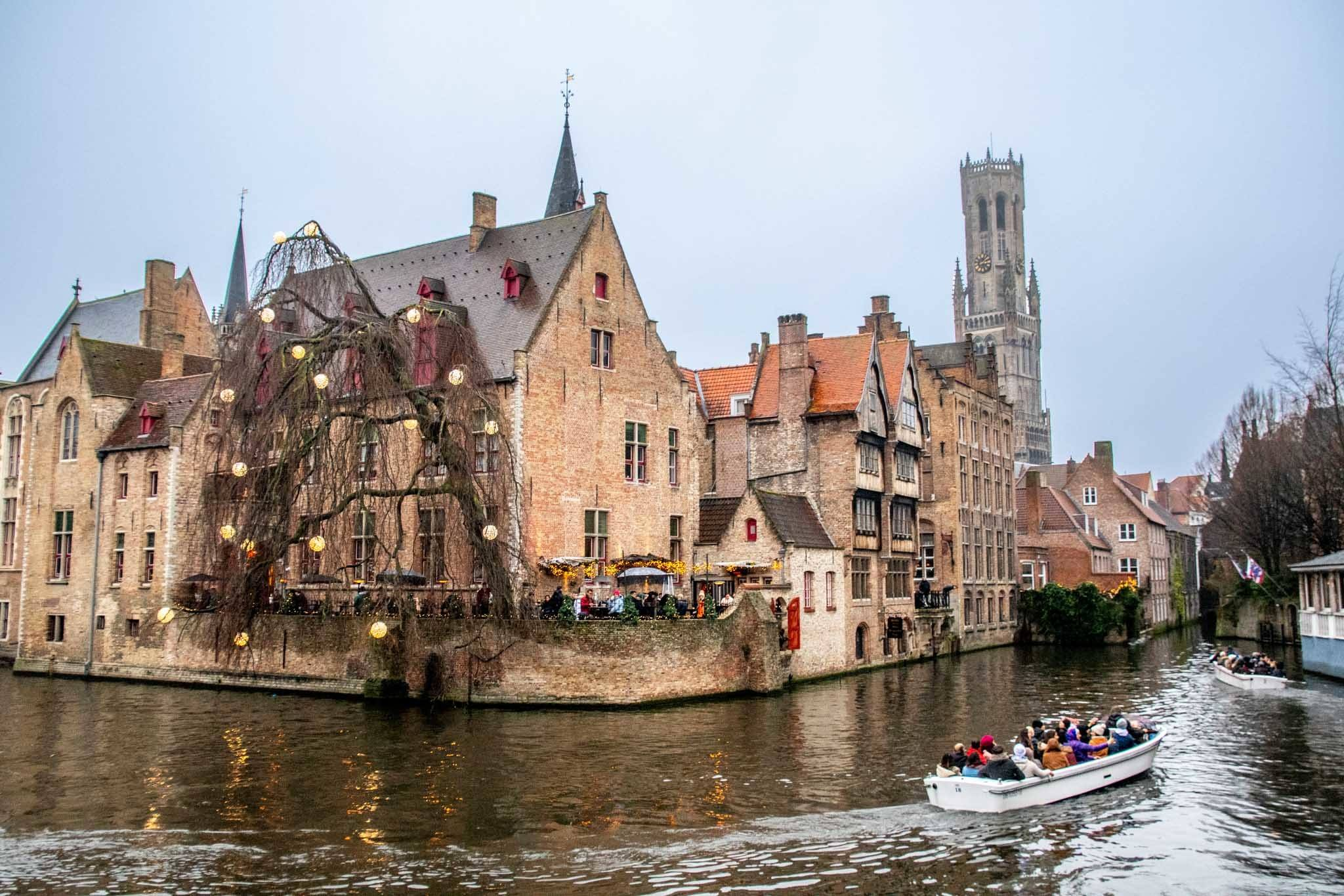 Two boats full of passengers in a canal in Bruges, Belgium