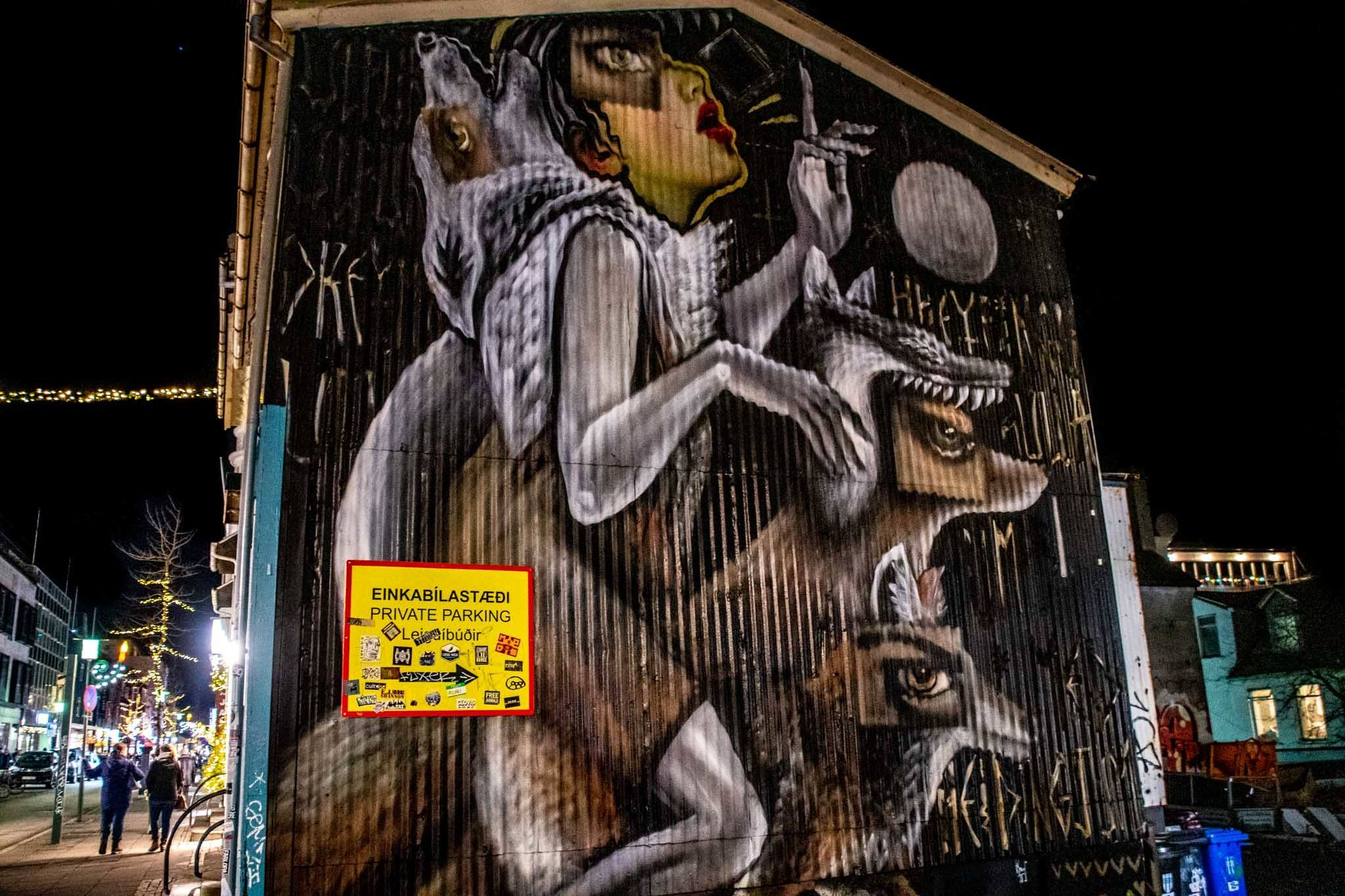 A street art mural featuring a woman and wolves