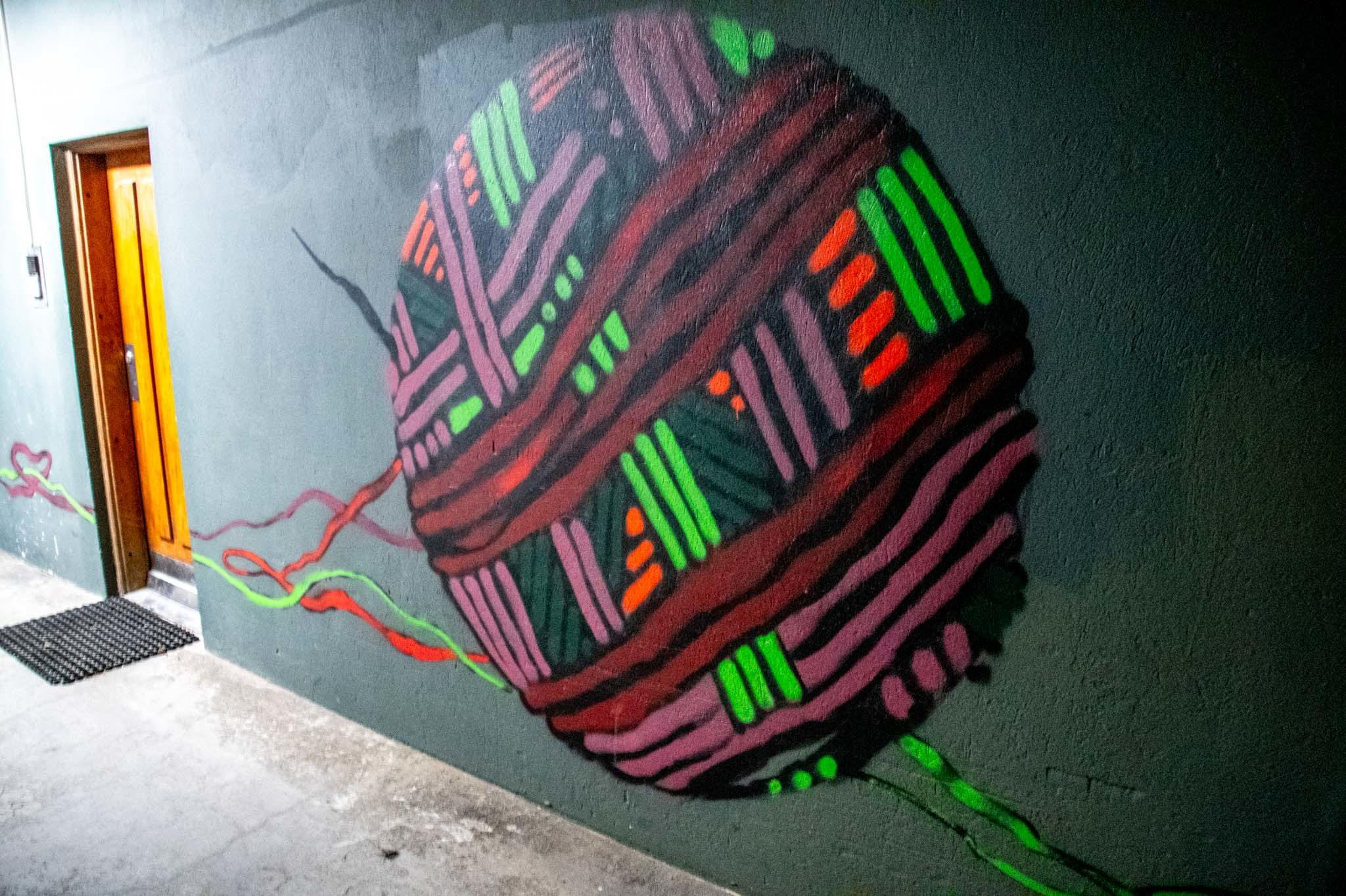 The ball of string is part of a two-part opposing mural.