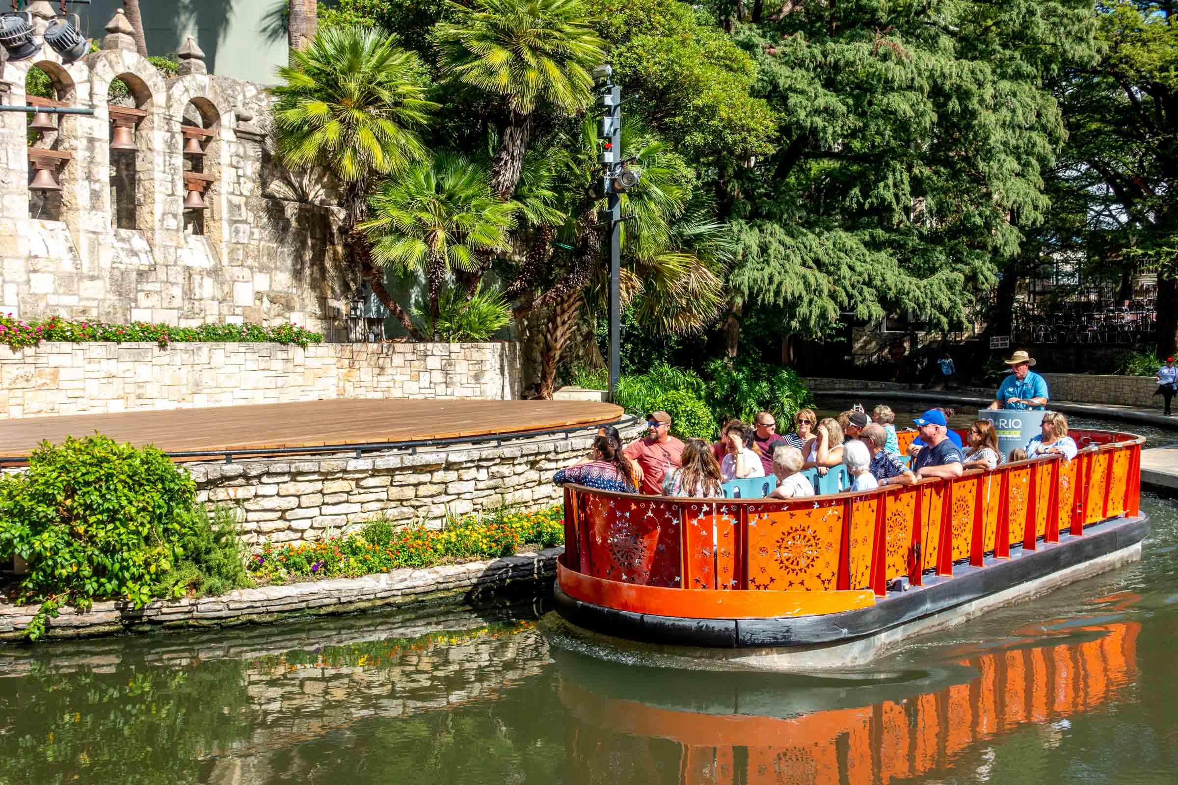 Orange boat filled with people in river along San Antonio RiverWalk