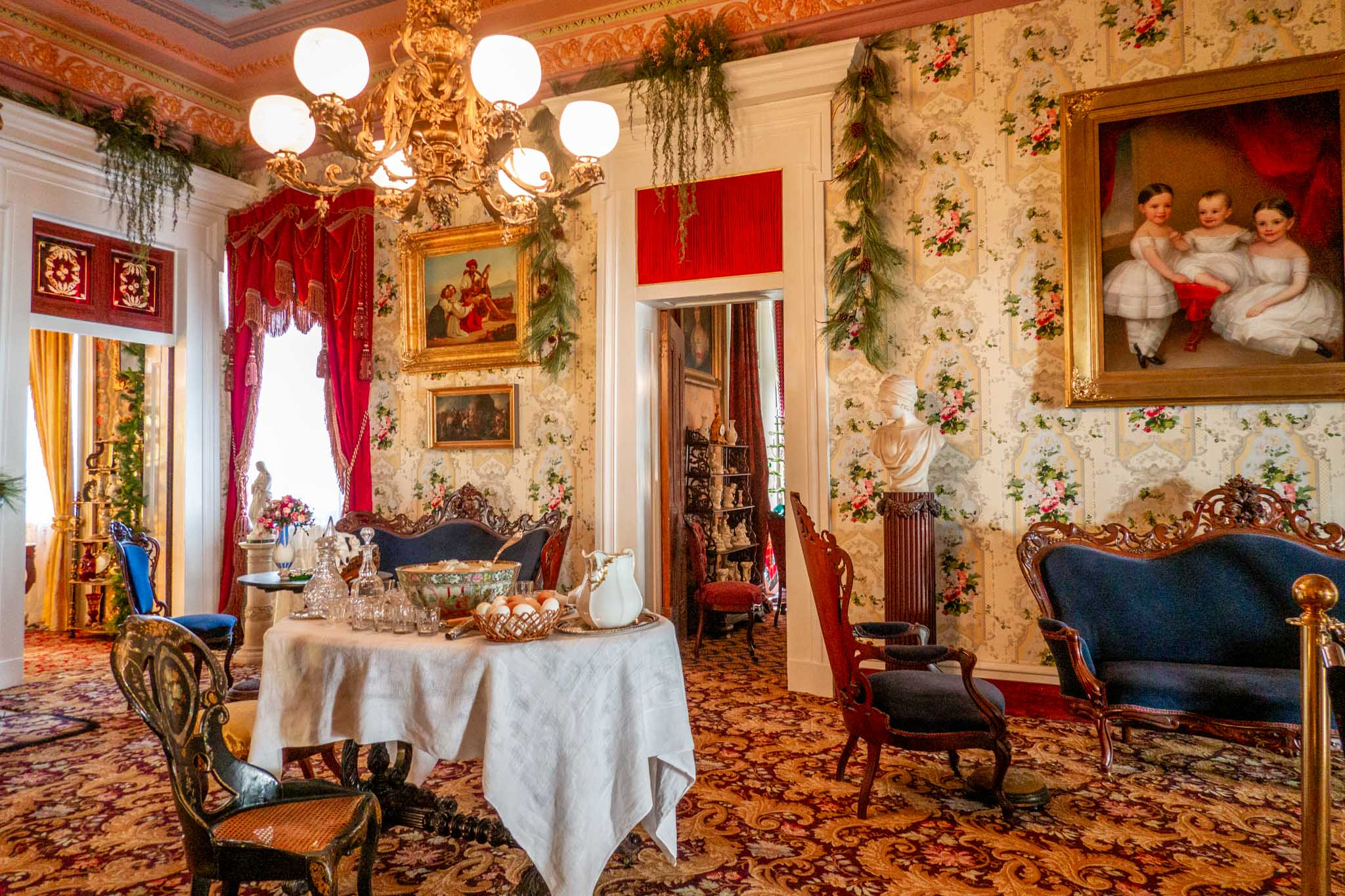 Sitting room with table, chairs, a portrait, and decorations at Belmont Mansion